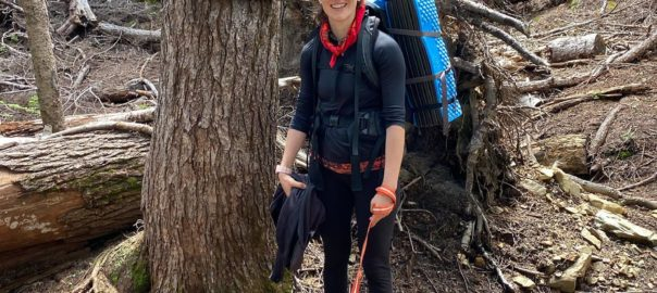 """Womam wearing glasses and backpacking gear with a leash and medium brown dog stands in a forest in front of a sign that reads """"Pacific Crest Trail No2000""""."""
