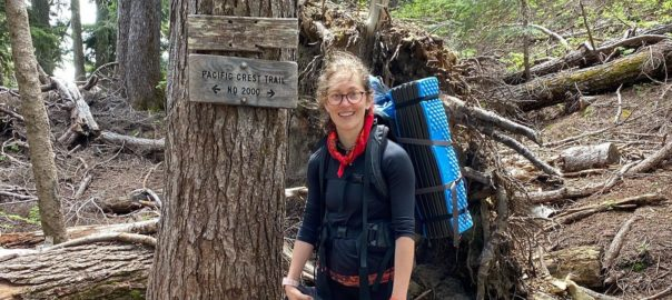 """Womam wearing glasses and backpacking gear stands in a forest in front of a sign that reads """"Pacific Crest Trail No2000""""."""