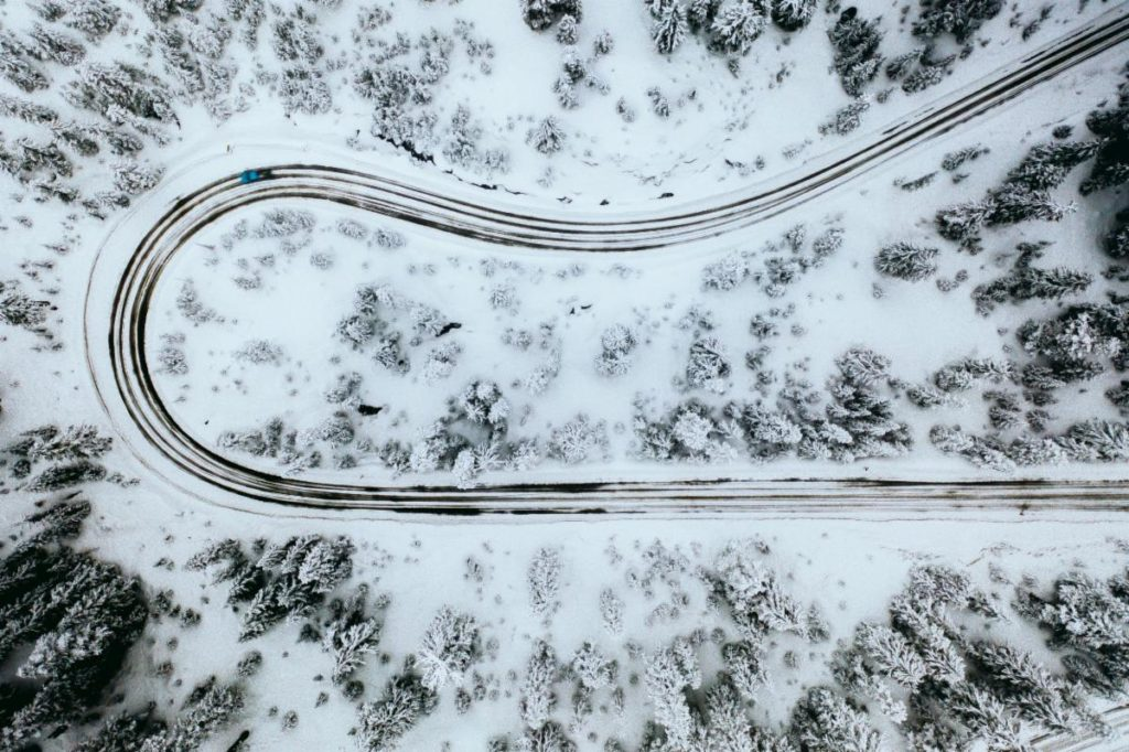 Photo of a winding road through snow and trees taken from an aerial view.