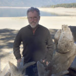 Image of Doug Kilgore, Man with grey beard and glasses, standing with drift wood in front of a body of water.